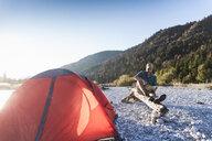 Mature man camping at riverside, looking on map - UUF16288