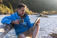 Mature man camping at riverside, using tablet - UUF16315