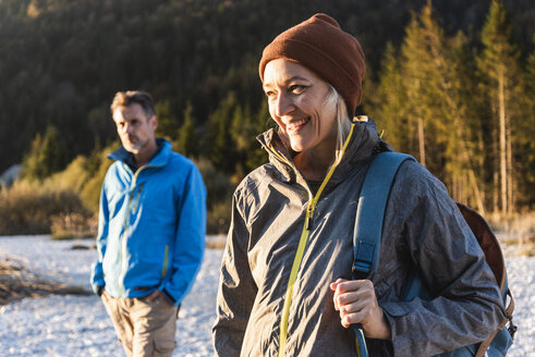 Mature couple hiking at riverside in the evening light - UUF16318