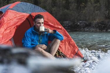 Mature man camping at riverside, drinking - UUF16327
