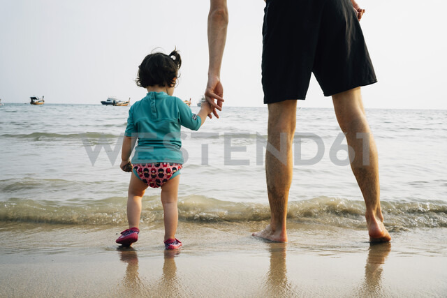 Thailand, Koh Lanta, back view of baby girl wearing UV protection shirt standing with her father at seashore - GEMF02649 - Gemma Ferrando/Westend61