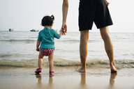 Thailand, Koh Lanta, back view of baby girl wearing UV protection shirt standing with her father at seashore - GEMF02649