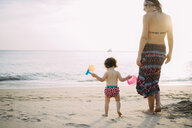Thailand, Koh Lanta, back view of baby girl and mother on the beach by sunset - GEMF02655