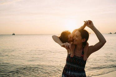 Thailand, Koh Lanta, happy mother with baby girl on her shoulders at seashore during sunset - GEMF02658