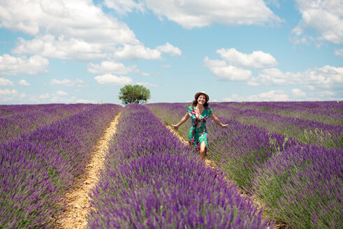 France, Provence, Valensole plateau, happy woman walking among lavender fields in summer - GEMF02662