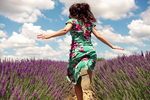 France, Provence, Valensole plateau, back view of woman running among lavender fields in summer - GEMF02668
