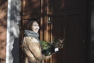 Brüssel, Belgium. Eine lachende Frau mit dem Korb mit Lebensmittel steht vor der Haustür. - KMKF00675