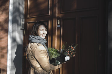 Portrait of laughing woman with cardboard box of purchases standing in front of house entrance - KMKF00675