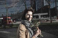 Brüssel, Belgium. Eine lachende Frau mit einem Blumenstrauß steht draußen und schaut im Objektiv an - KMKF00678