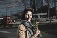 Portrait of smiling woman with bunch of flowers in the city - KMKF00678