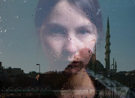 Young woman looking through a window with a mosque reflection - INGF09860