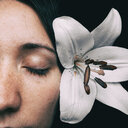 Close-up shot of a woman with a fragile white flower in her hair - INGF09958