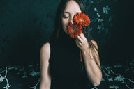 Midsection of a young woman holding flowers to her face - INGF09976