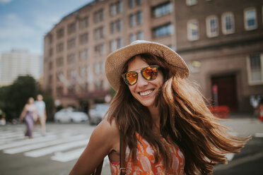 A smiling young woman wearing sunglasses in the city - INGF10018