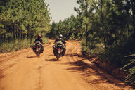Rear view of male friends riding motorcycles on dirt road during sunny day - CAVF59862