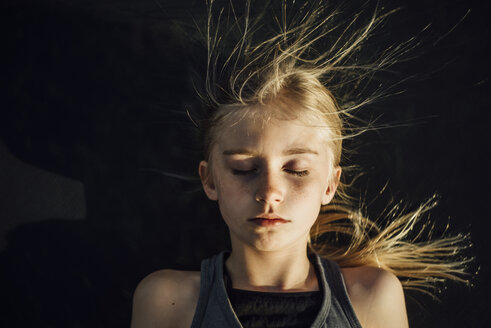 Overhead view of girl with eyes closed and tousled hair during sunny day - CAVF59877