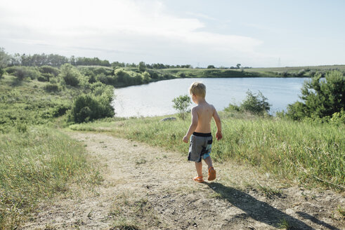 Rear view of shirtless boy walking on field by lake against sky - CAVF59901