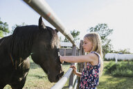 Side view of girl stroking horse at barn - CAVF59904