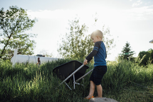 Side view of boy holding wheelbarrow while standing on grassy field against sky - CAVF59907