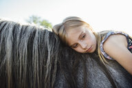 Side view of thoughtful girl lying on horse against clear sky - CAVF59910