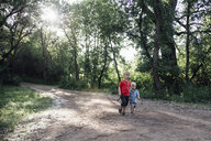 Brothers walking on dirt road in forest - CAVF59913