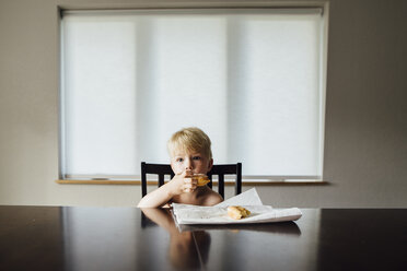 Portrait of shirtless boy eating bread while sitting by table at home - CAVF59919