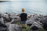 Rear view of boy standing at rocky beach - CAVF59922