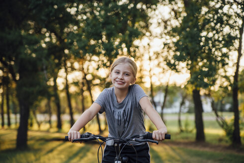 Portrait of girl riding bicycle at park - CAVF59937