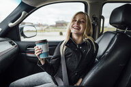 Cheerful girl holding disposable cup while sitting in car - CAVF59961