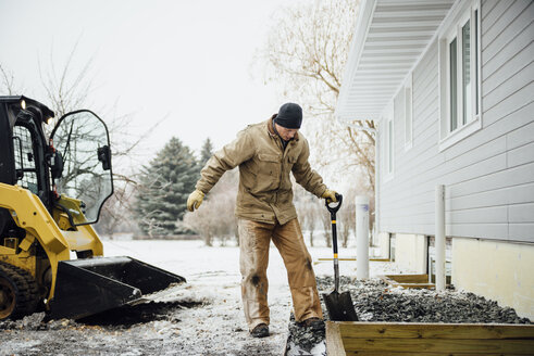 Man holding shovel working in backyard against sky during winter - CAVF59973
