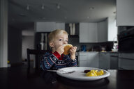 Portrait of baby boy eating food while sitting by dining table at home - CAVF59976