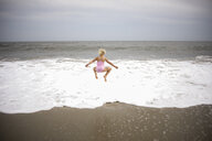 Rear view of playful girl jumping on shore at beach against sky - CAVF60006
