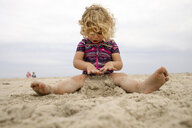 Full length of girl playing with sand at beach against sky - CAVF60009
