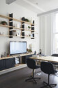 Shelves over television set by furniture in modern office - CAVF60116