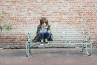 Full length portrait of boy wearing jacket while crouching on bench at footpath against brick wall - CAVF60131