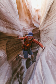 Full length portrait of hiker canyoneering amidst narrow canyons - CAVF60152