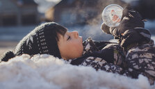 Side view of boy with snow globe lying outdoors during winter - CAVF60185
