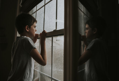 Side view of thoughtful boy looking through wet window reflecting on mirror at home - CAVF60188