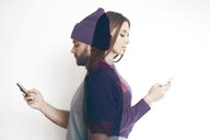 Double exposure of man and woman using mobile phones against white background - CAVF60296