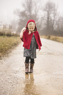 Girl in warm clothing walking on puddle - CAVF60308
