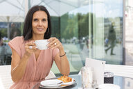 Portrait of smiling mature woman drinking coffee at pavement cafe - JUNF01583