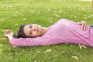Portrait of smiling mature woman wearing pink shirt relaxing on a meadow in summer - JUNF01586