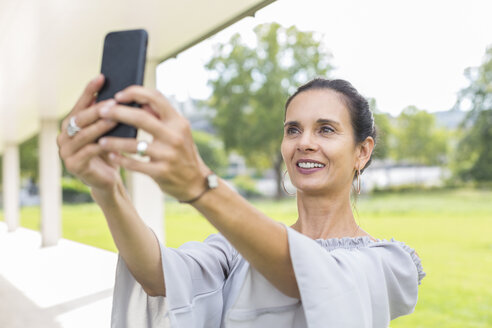 Portrait of smiling mature woman taking selfie with smartphone outdoors - JUNF01598