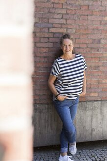 Portrait of smiling mature woman leaning against brick wall in summer - JUNF01613