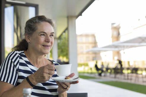 Portrait of smiling mature woman drinking cup of coffee on terrace - JUNF01622