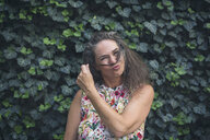 Portrait of mature woman standing in front of wall overgrown with ivy pouting mouth - JUNF01631
