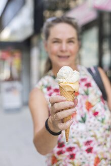 Woman's hand holding ice cream cone, close-up - JUNF01634