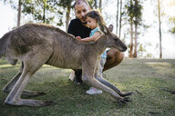 Australia, Brisbane, father and little daughter stroking tame kangaroo - GEMF02672