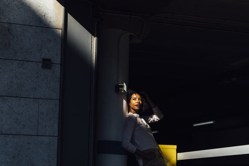 Young casual businesswoman at car park, sunlight and shadow - BOYF01263