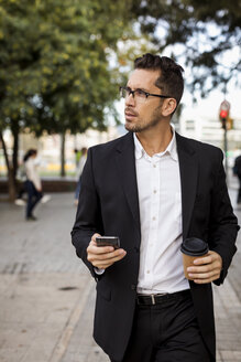 Businessman with takeaway coffee and cell phone in the city on the go - MAUF01935